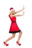 Santa Girl pushing the wall Stock Photography