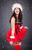 Sexy santa girl in red dress over snowy Christmas background Stock Photo
