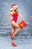 Sexy Santa girl in a red swimsuit with a Christmas hat on the snow Royalty Free Stock Photos