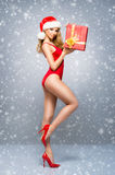 Sexy Santa girl in a red swimsuit with a Christmas hat on the snow Stock Photography