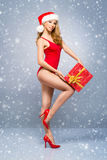 Sexy Santa girl in a red swimsuit with a Christmas hat on the snow Royalty Free Stock Images