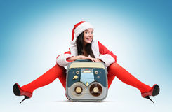 Sexy Santa girl with vintage tape recorder. On blue background Stock Images