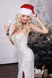 Sexy Santa girl wears luxurious dress,holding glass of champagne Royalty Free Stock Photo
