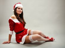 Santa helper lying down. Santa helper girl in Christmas costume lying down royalty free stock image