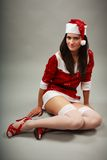 Santa helper lying down. Santa helper girl in Christmas costume lying down stock photos