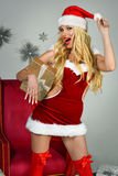 Sexy Santa Helper model with gifts. Young beautiful girl wearing Christmas outfit Stock Photo