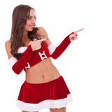 Sexy santa pointing to her side Royalty Free Stock Photography
