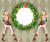Sexy Santa's helper frame. Beautiful twins in sexy Santa suits bordering a holiday wreath frame Stock Image