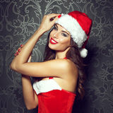 Sexy santa woman in red hat. Posing at vintage wall Royalty Free Stock Photos