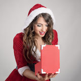 Sexy Santa woman with red hooded costume opening Christmas present with excited expression Royalty Free Stock Images