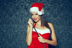 santa woman with red lips in hat posing indoor with whip at stock image