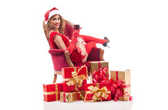 Sexy santa woman sitting on a chair with a glass of wine in hand Stock Images