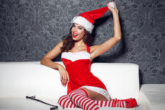 Sexy santa woman with whip pulling hat Stock Photo