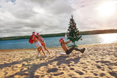 Sexy Santas  pulling Santa at the beach Stock Image