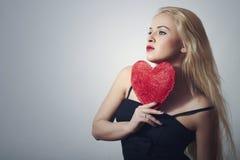 Sexy schöne blonde Frau mit rotem Herzen. Schönheits-Mädchen. Zeigen Sie Liebes-Symbol. Das Day.Passion des Valentinsgrußes Lizenzfreie Stockfotos