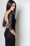 Sexy schöne elegante Frau mit dem langen Haar, helles Abendmake-up in einem schwarzen Abendkleid im Studio auf einem weißen Hinte Lizenzfreie Stockfotos