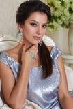 schöne junge Brunettefrau mit dem Abendmake-upchic gepflegt, ein kurzes Abendkleid tragend gestickt mit Silber Stockfotos