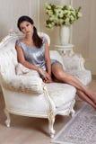 schöne junge Brunettefrau mit dem Abendmake-upchic gepflegt, ein kurzes Abendkleid tragend gestickt mit Silber Stockbilder