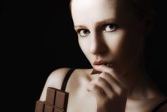 Sexy schöne junge Frau, die Schokolade auf einer Dunkelheit isst stockfotografie