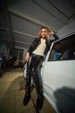 Sexy schönes blondes Mädchen in der ledernen Kleidung in der Garage Lizenzfreies Stockfoto
