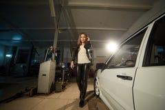 Sexy schönes blondes Mädchen in der ledernen Kleidung in der Garage Lizenzfreie Stockbilder