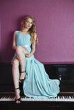 Sexy schönes blondes Mädchen im Kleid, das Klavier spielt Stockbilder