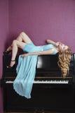Sexy schönes blondes Mädchen im Kleid, das Klavier spielt Stockfoto