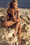 Sexy schönes Mädchen mit dem blonden Haar im Bikini, der auf Strand sich entspannt Lizenzfreie Stockfotos