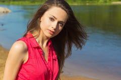 Sexy schönes Mädchen mit dem langen dunklen Haar, das in den Denimkurzen hosen auf dem Strand am sonnigen Tag sitzt Stockfotos