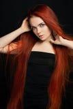 Sexy schönes Rothaarigemädchen mit dem langen Haar Perfektes Frauenporträt auf schwarzem Hintergrund Herrliches Haar und tiefe Au lizenzfreie stockfotografie