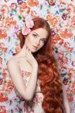 Sexy schönes Rothaarigemädchen mit dem langen Haar Perfektes Frauenporträt mit einem farbigen hellen Hintergrund Herrliches Haar  Stockfotografie