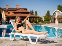 Sexy, Schönheit, die im Bikini auf einem Swimmingpoolhintergrund liegt Sommerhotelkonzept Kopieren Sie Platz stockfotografie