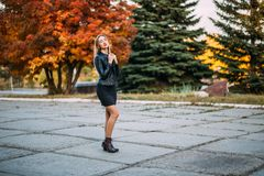 Sexy Schönheit im schwarzen kurzen Kleid und in der Lederjacke draußen stockbild