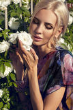 Sexy Schönheit mit dem blonden Haar, das am Garten der Rose aufwirft Lizenzfreies Stockfoto