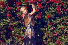 Sexy Schönheit mit dem blonden Haar, das am Garten der Rose aufwirft Stockfotografie