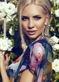 Sexy Schönheit mit dem blonden Haar, das am Garten der Rose aufwirft Stockbilder