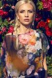 Sexy Schönheit mit dem blonden Haar, das am Garten der Rose aufwirft Lizenzfreie Stockbilder