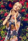 Sexy Schönheit mit dem blonden Haar, das am Garten der Rose aufwirft Stockfotos