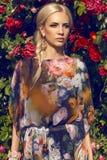 Sexy Schönheit mit dem blonden Haar, das am Garten der Rose aufwirft Lizenzfreies Stockbild