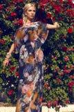 Sexy Schönheit mit dem blonden Haar, das am Garten der Rose aufwirft Lizenzfreie Stockfotos