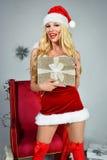 Sexy schöne Blondine, die in Santa Claus-Kostüm aufwerfen Stockfotos