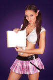 Sexy schoolgirl holding an open book showing a blank paper. Copyspace Stock Photo