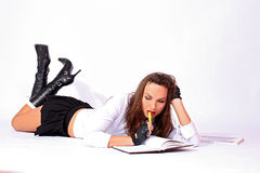 Sexy schoolgirl laying on the floor Royalty Free Stock Images