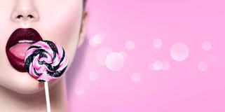 Sexy schoonheidsmeisje die lolly eten Glamour modelvrouw die zoet kleurrijk lollysuikergoed likken stock foto's