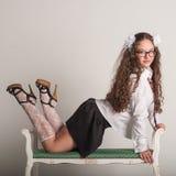 Sexy Schulmädchen, das auf Sofa aufwirft Lizenzfreie Stockfotos
