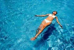 Sexy Schwimmendame mit der Bikinireihe, die auf Wasser schwimmt lizenzfreie stockfotografie