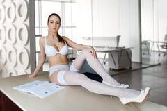 Sexy secretaressezitting op bureau in bureau Stock Foto's