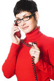 Secretary. A young woman with charming big green eyes is bearing modern glasses and receiving calls on a landline phone Stock Photography