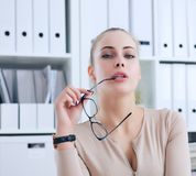 Sexy secretary with glasses in hand undresses in office, flirt and desire. Office provocation. Sexy secretary in glasses undress in office, flirt and desire Royalty Free Stock Photography