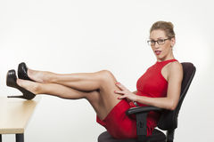 Sexy secretary sitting with her feet on the desk Royalty Free Stock Images